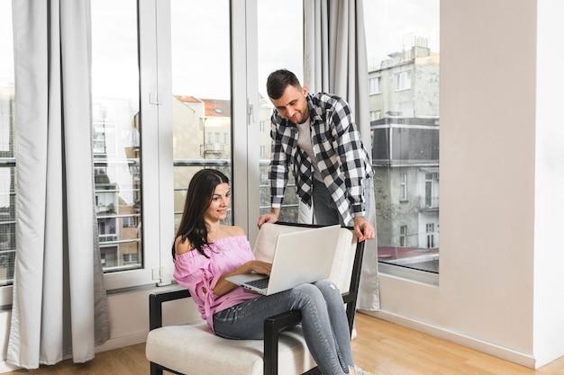 Jonge man op zoek naar zijn vriendin met behulp van laptop thuis