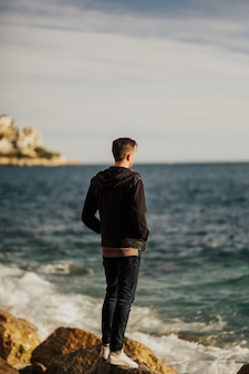 Jonge man op zoek op de zee vanaf de kust in zonnige dag.