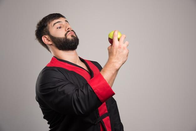 Jonge man op zoek op een verse appel.