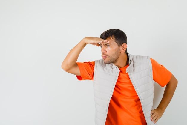 Jonge man op zoek ver weg met hand boven het hoofd in t-shirt, jasje vooraanzicht.
