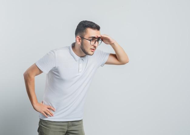 Jonge man op zoek ver weg met hand boven het hoofd in wit t-shirt, broek en op zoek gericht