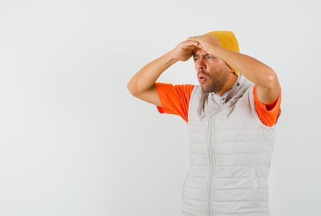 Jonge man op zoek ver weg met handen boven het hoofd in t-shirt, jasje, hoed en op zoek gericht, vooraanzicht.