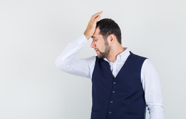 Jonge man opgeheven hand leunend op voorhoofd in shirt, vest en spijtig op zoek