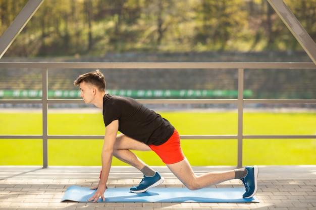 Jonge man opleiding yoga buitenshuis. sportieve man maakt rekoefeningen op een blauwe yogamat, op het sportveld.