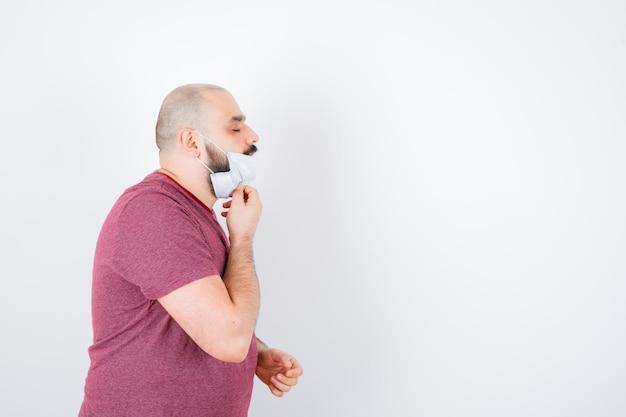 Jonge man opstijgen zijn masker in roze t-shirt, masker.