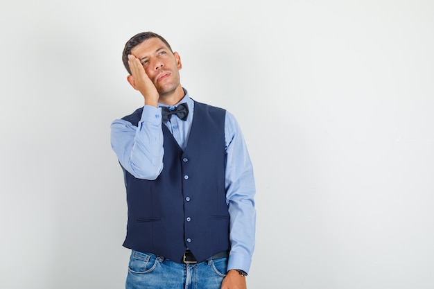 Jonge man opzoeken met de hand op zijn wang in pak, spijkerbroek en peinzend kijken.