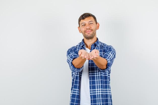 Jonge man outstretching cupped handen in shirt en kijkt vrolijk, vooraanzicht.