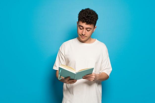 Jonge man over blauw een boek te houden en te genieten van het lezen