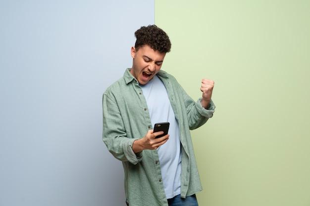 Jonge man over blauw en groen vieren een overwinning met een mobiel