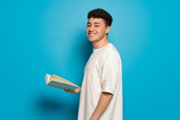 Jonge man over blauwe achtergrond een boek te houden en te genieten van het lezen