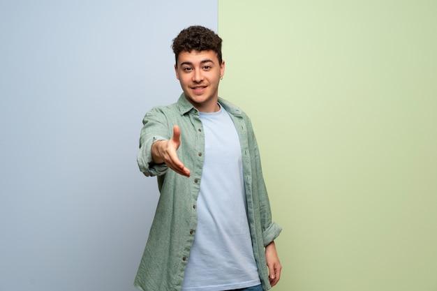 Jonge man over blauwe en groene achtergrond handen schudden voor het sluiten van een goede deal