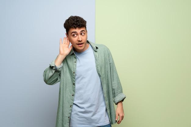 Jonge man over blauwe en groene achtergrond luisteren naar iets door hand op het oor te zetten