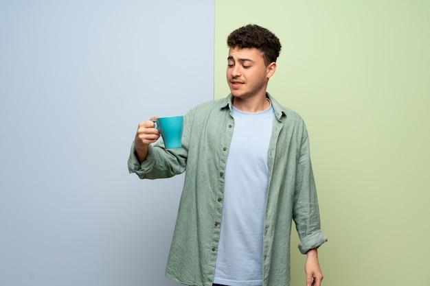 Jonge man over blauwe en groene muur met een warme kop koffie