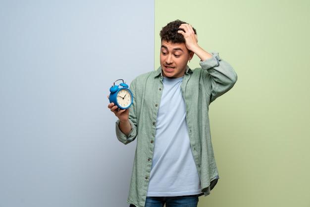 Jonge man over blauwe en groene muur onrustig omdat het laat is geworden en vintage wekker houdt