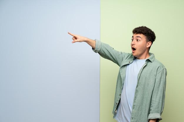 Jonge man over blauwe en groene muur weg wijzen