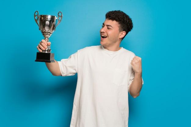 Jonge man over blauwe muur met een trofee
