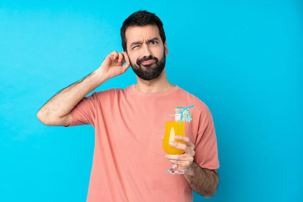 Jonge man over een cocktail met twijfels te houden
