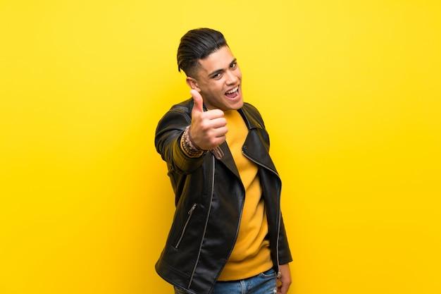 Jonge man over geïsoleerde gele muur met duimen omhoog omdat er iets goeds is gebeurd