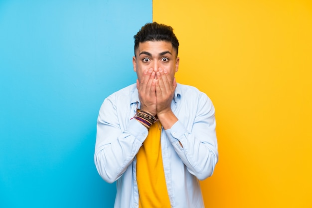 Jonge man over geïsoleerde kleurrijke achtergrond met verrassing gelaatsuitdrukking