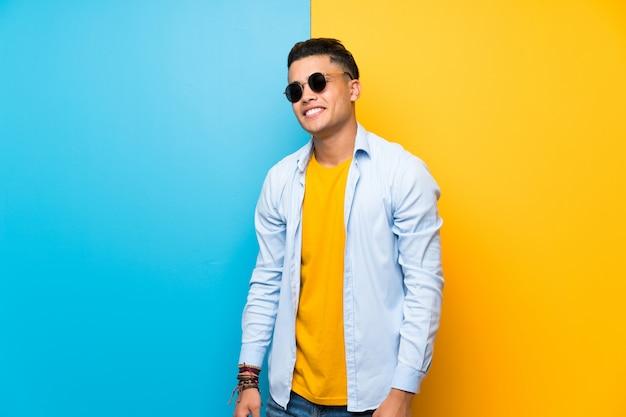 Jonge man over geïsoleerde kleurrijke achtergrond met zonnebril