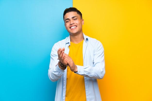 Jonge man over geïsoleerde kleurrijke muur applaudisseren