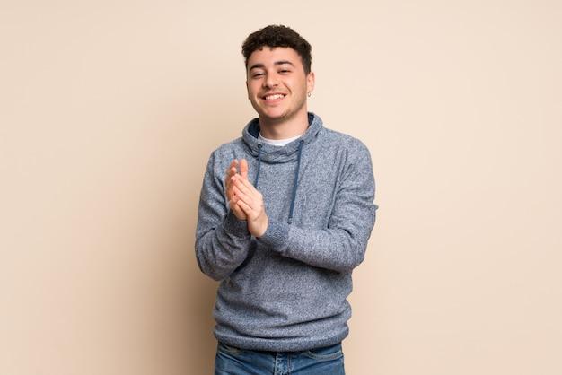 Jonge man over geïsoleerde muur applaudisseren na presentatie in een conferentie