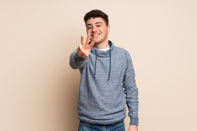Jonge man over geïsoleerde muur gelukkig en drie met vingers tellen