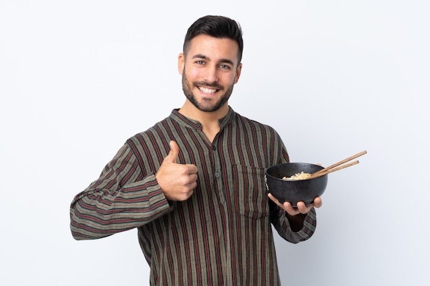 Jonge man over geïsoleerde muur met duimen omhoog omdat er iets goeds is gebeurd terwijl je een kom noedels met eetstokjes vasthield