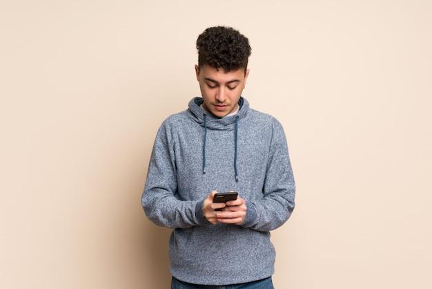 Jonge man over geïsoleerde muur verzenden van een bericht met de mobiel