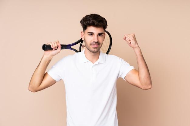 Jonge man over geïsoleerde tennissen en het vieren van een overwinning