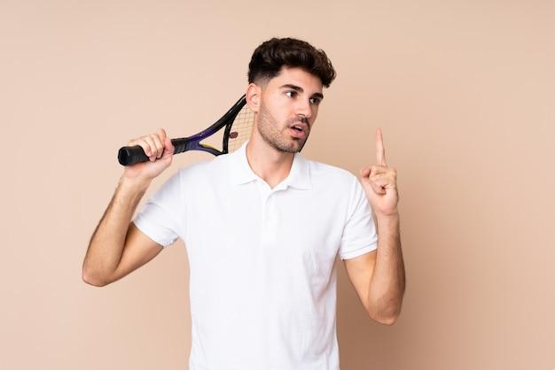 Jonge man over geïsoleerde tennissen en omhoog
