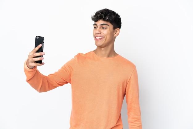 Jonge man over geïsoleerde witte achtergrond een selfie maken