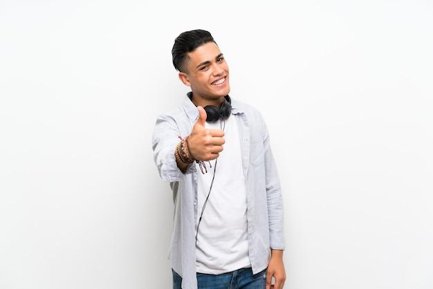Jonge man over geïsoleerde witte muur met oortelefoons met duimen omhoog omdat er iets goeds is gebeurd