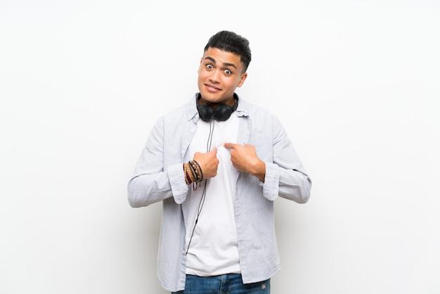Jonge man over geïsoleerde witte muur met oortelefoons met verrassing gelaatsuitdrukking