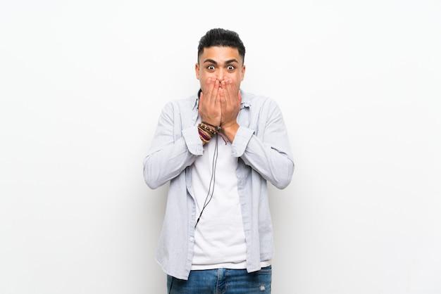 Jonge man over geïsoleerde witte muur met oortelefoons met verrassingsgelaatsuitdrukking