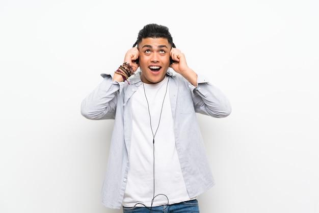 Jonge man over geïsoleerde witte muur met oortelefoons