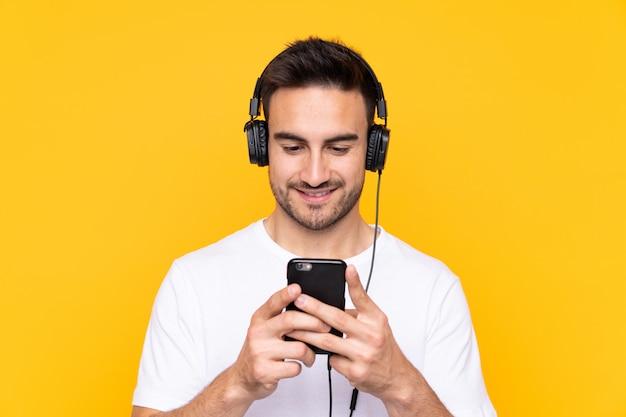 Jonge man over gele muur luisteren muziek en kijken naar mobiel