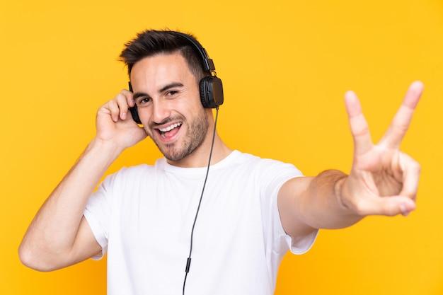 Jonge man over gele muur luisteren muziek en zingen