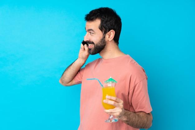 Jonge man over het houden van een cocktail houden van een gesprek met de mobiele telefoon met iemand