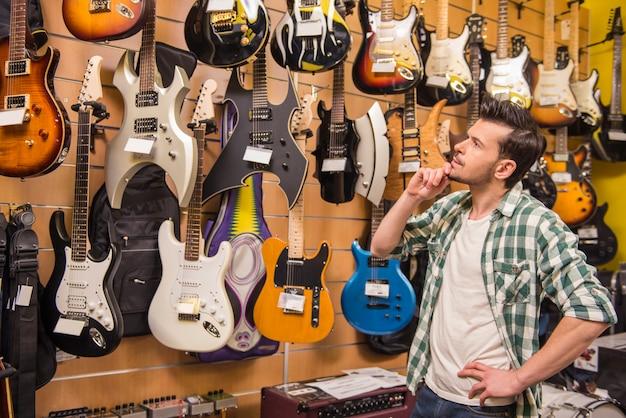 Jonge man overweegt elektrische gitaren muziekwinkel.