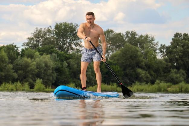 Jonge man paddleboarden op een rivier overdag