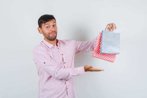 Jonge man papieren zakken in shirt tonen en vrolijk kijken. vooraanzicht.