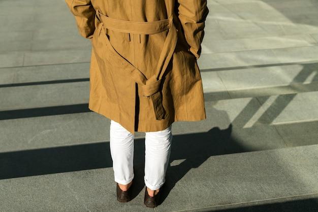 Jonge man permanent buiten en modieuze bruine jas dragen.