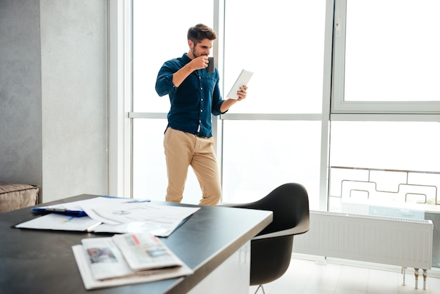 Jonge man permanent in de buurt van raam en koffie drinken tijdens het lezen van de krant