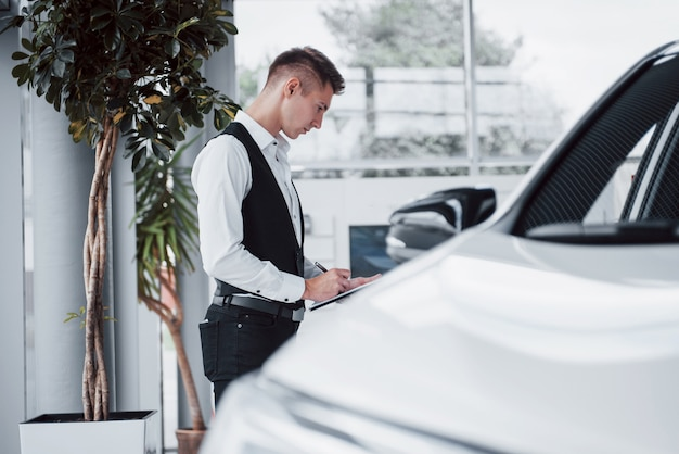 Jonge man permanent in de showroom tegen auto's
