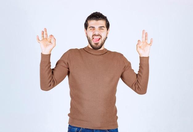 Jonge man permanent met gesloten ogen en ok gebaar tonen.