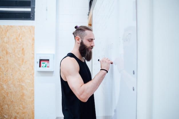 Jonge man personal trainer indoor gym schrijven op whiteboard planning training