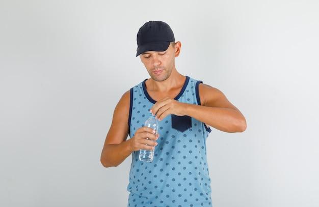 Jonge man plastic dop van waterfles openen in blauw hemd met dop