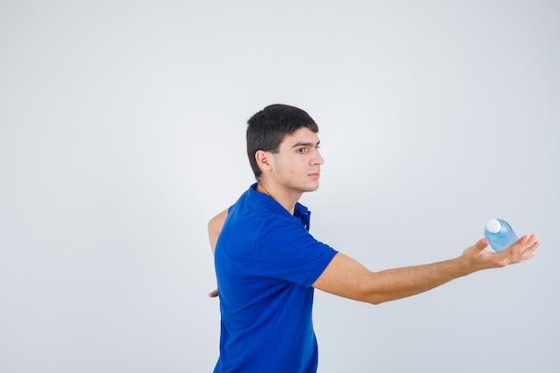 Jonge man plastic fles in de hand houden in t-shirt en voorzichtig kijken.