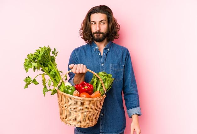 Jonge man plukken biologische groenten uit zijn tuin geïsoleerd verward, twijfelachtig en onzeker.
